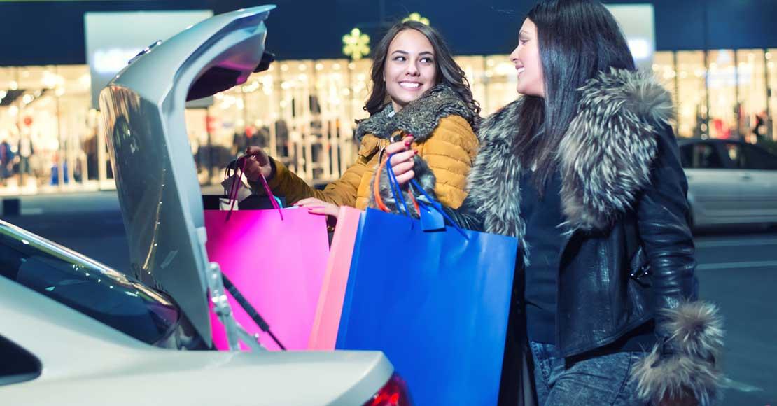 to kvinner med handleposer ved bagasjerom